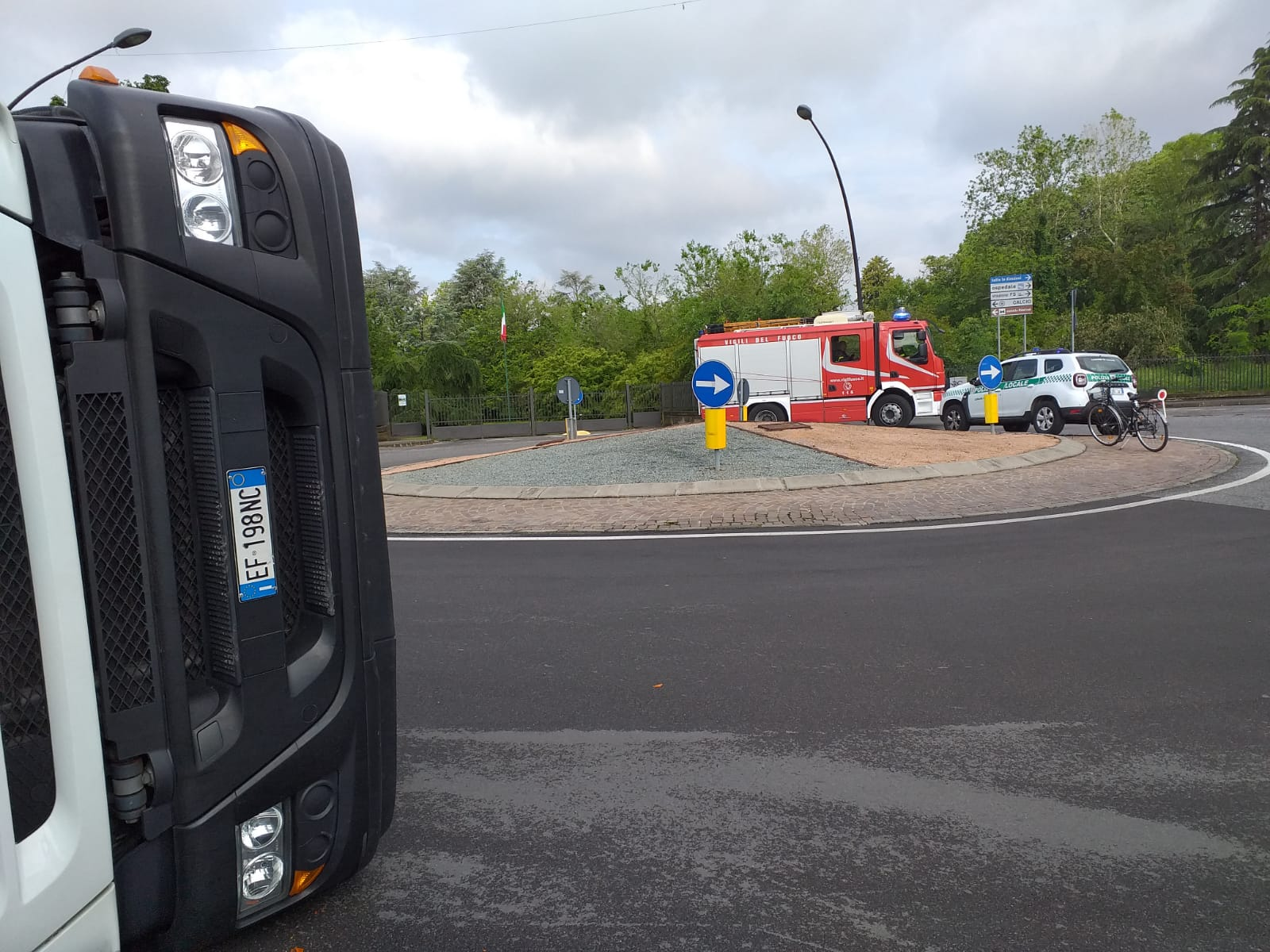 Camion dei rifiuti si ribalta in rotonda, traffico