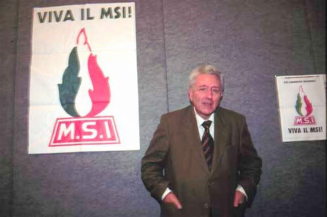 Pino Rauti davanti a due manifesti del Movimento sociale Italiano