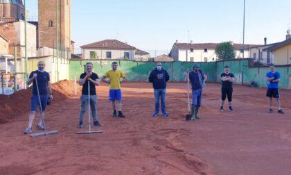 Volontari al lavoro sul campo da tennis