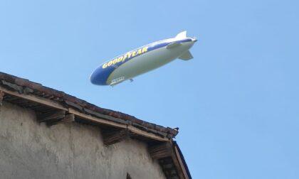 Un enorme dirigibile in volo sulla pianura e sull'Adda